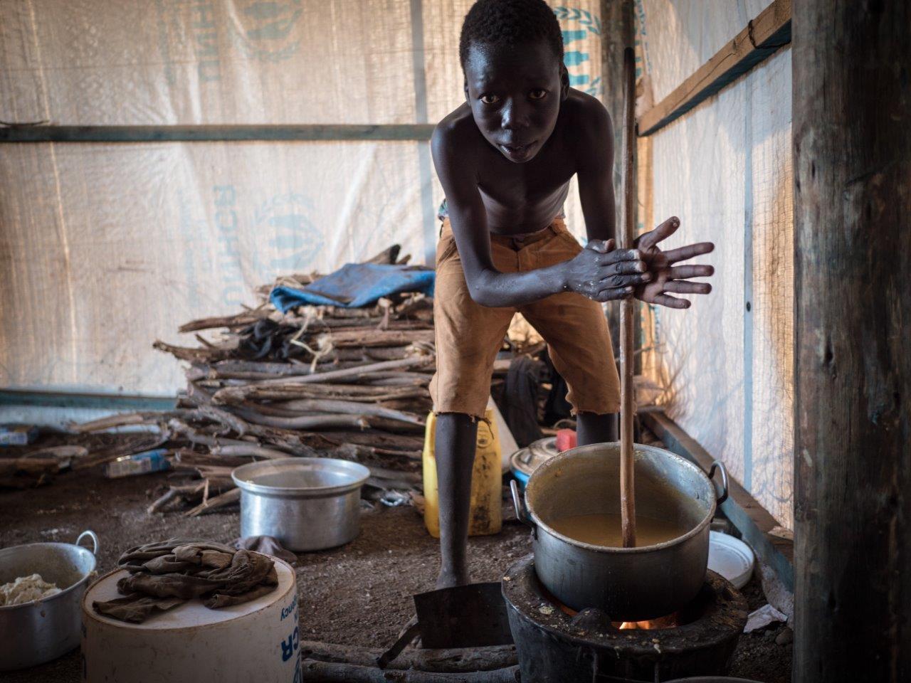 Flüchtlingsjunge aus dem Südsudan bereitet Maisbrei zu (Credit: Aktion Deutschland Hilft /Roland Brockmann)