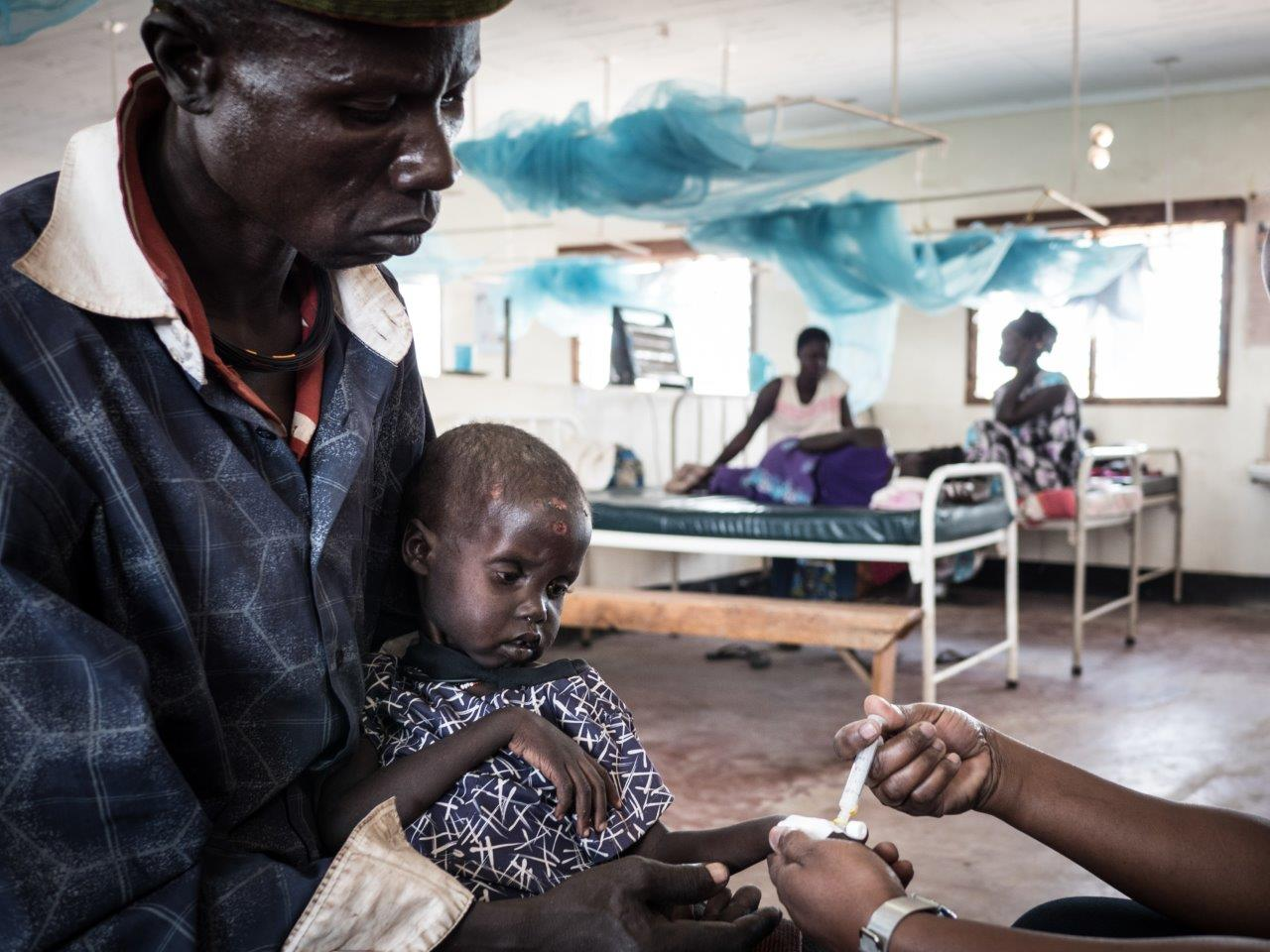 Turkana mit seiner an Malaria leidenden Tochter im von den Johannitern betriebenen Krankenhaus von Kakuma (Credit: Aktion Deutschland Hilft /Roland Brockmann)